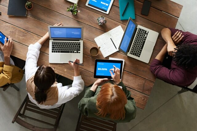Group of people working on laptops with blue screens at large table | SEO service Cleveland Ohio