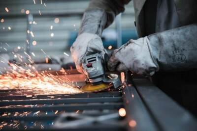 Industrial worker using power grinder on metal causing sparks to fly | Industrial web design