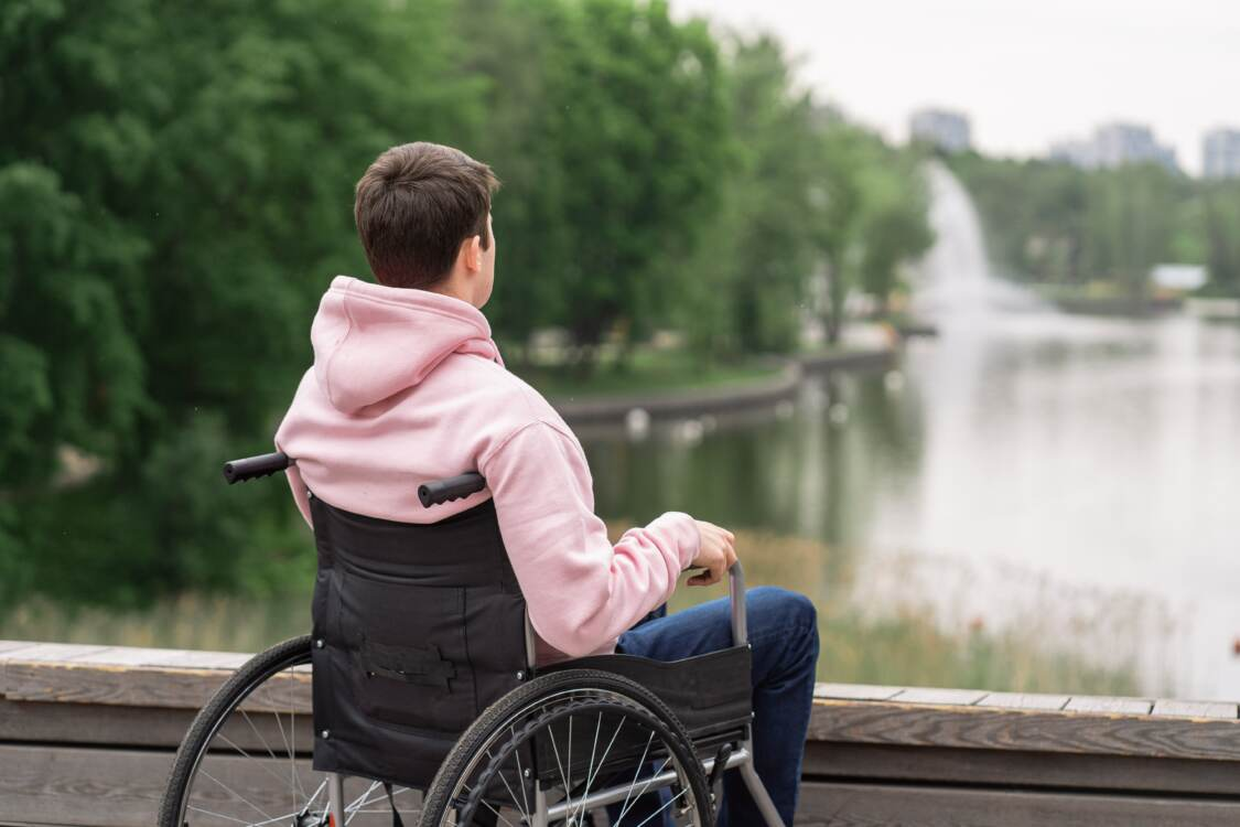 a young man in a wheel chair by a lake