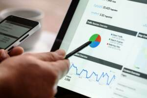 Someone pointing to graphs on laptop with a stylus | SEO Packages