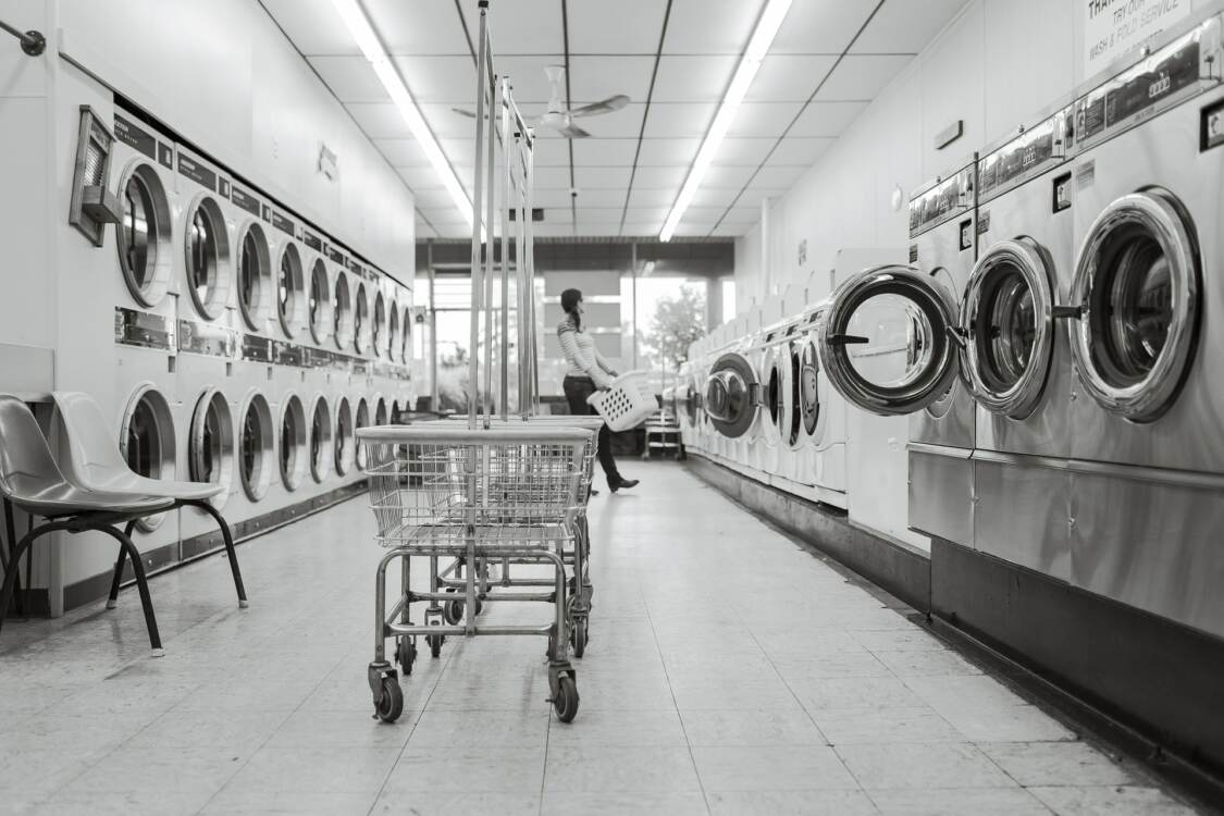 An empty cart in a laundromat with many washers and dryers on either side | Commercial laundry equipment