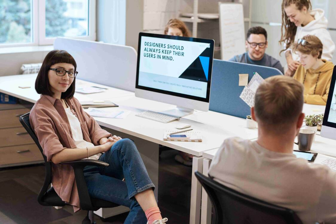 Team of marketing specialists and graphic designers working around a long desk with multiple computers | Marketing companies near me