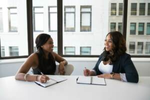 Website design near me | Two women working at a table and smiling