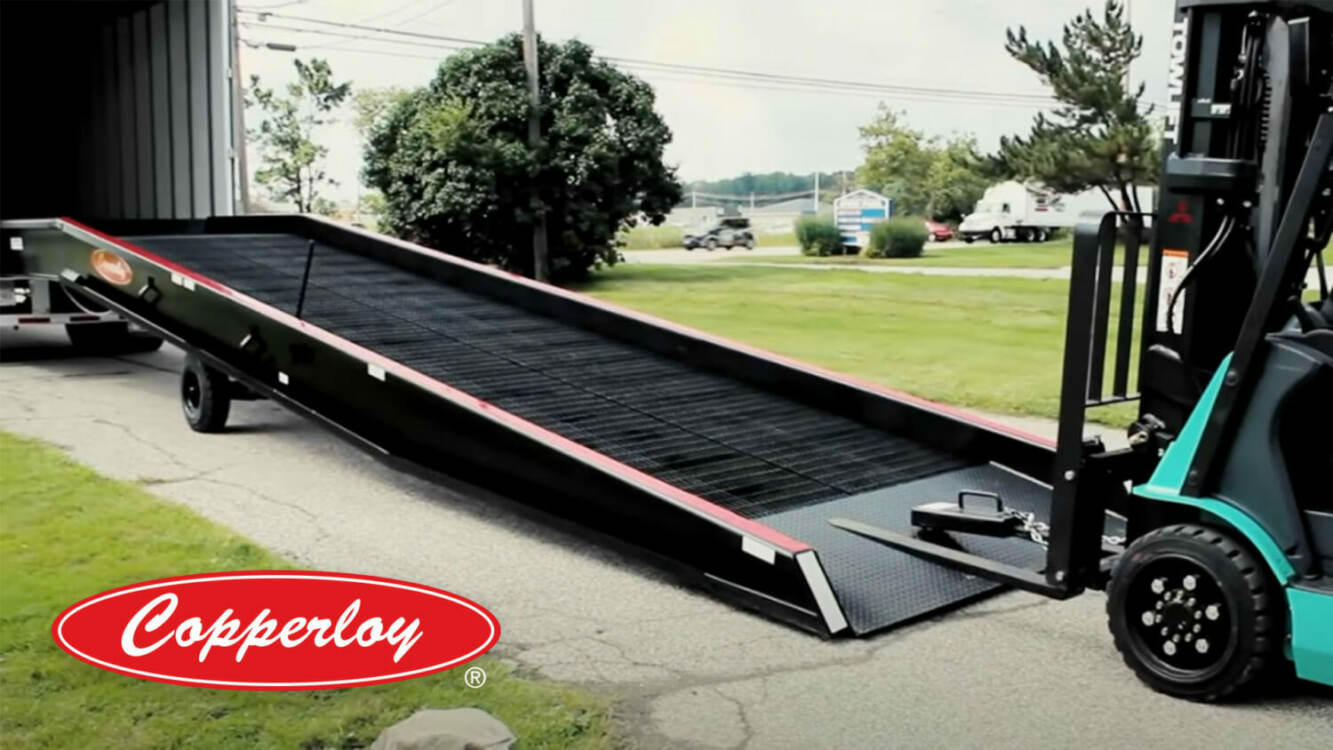 Copperloy Yard Ramp Rentals | A yard ramp linked to a truck bed with a forklift preparing to travel up it.