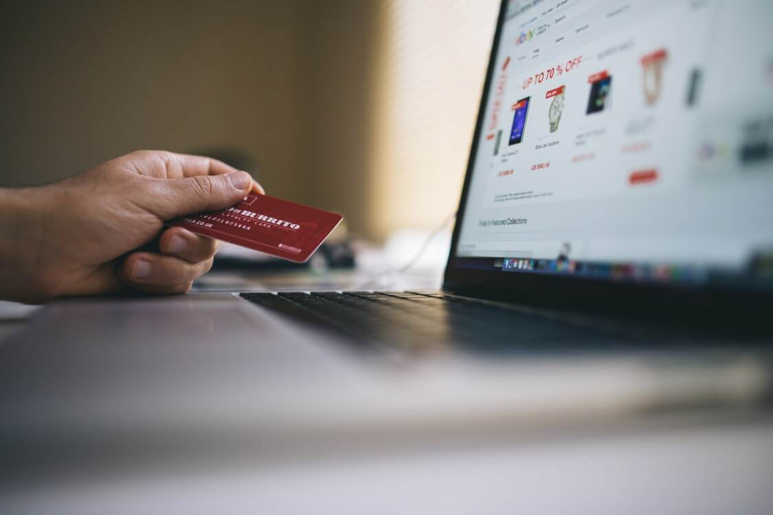 A person holding a credit card next to their laptop | Akron web design services