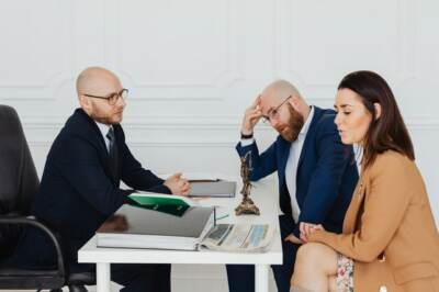 Three people chatting at a desk   Social security disability attorneys